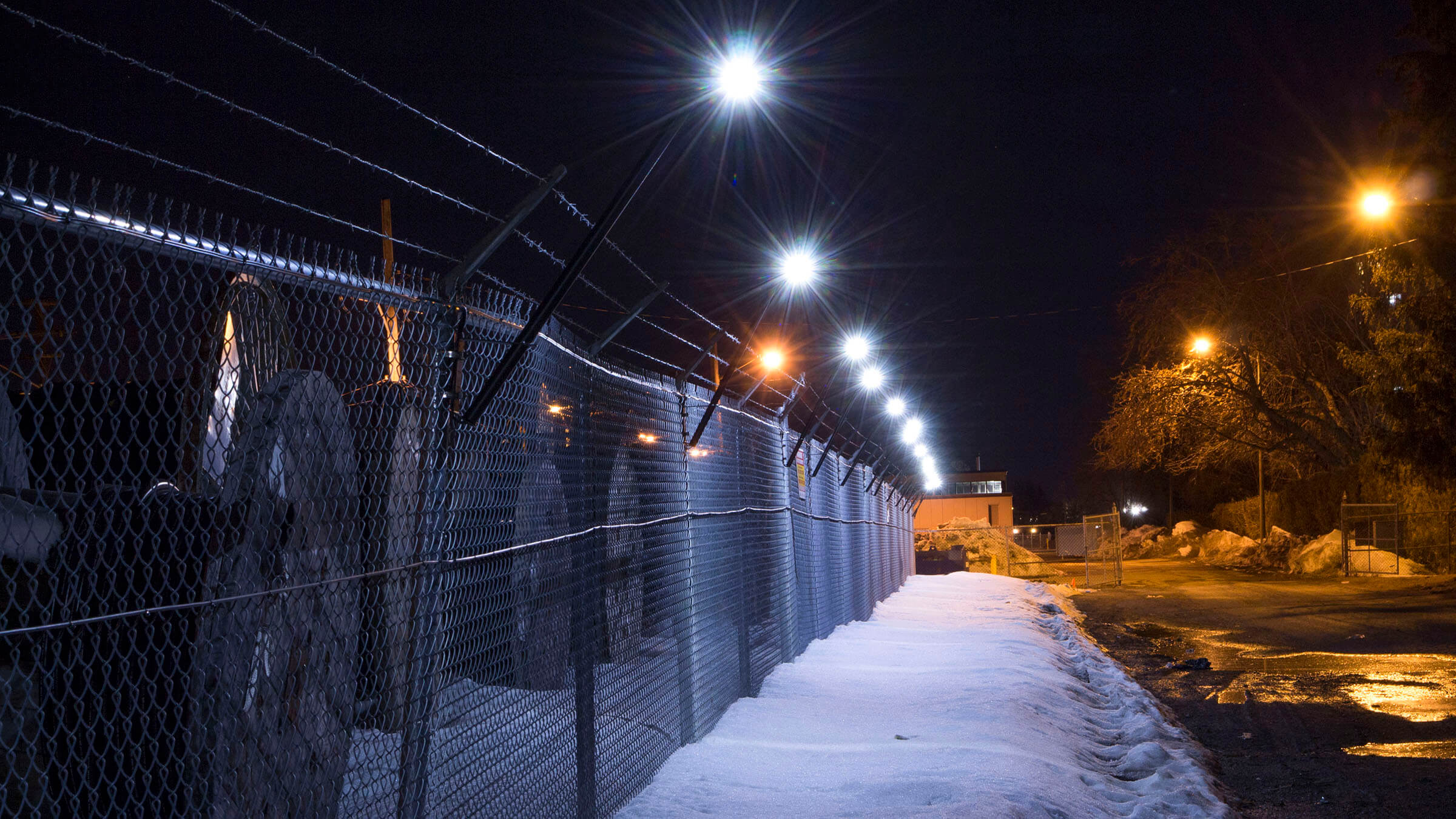 Senstar LM100 hybrid perimeter intrusion detection and intelligent lighting system and FlexZone fence-mounted intrusion detection sensor along the fence surrounding an electrical utility site to show examples of Senstar's innovative security solutions