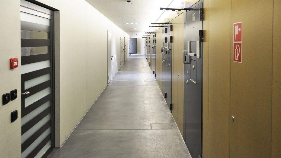 Korrigierter Flur mit Zellentüren auf der rechten Seite und einer Tür auf der linken Seite mit Schlüsselkarten, um die Zutrittskontrollfunktionen von Senstar zu demonstrieren