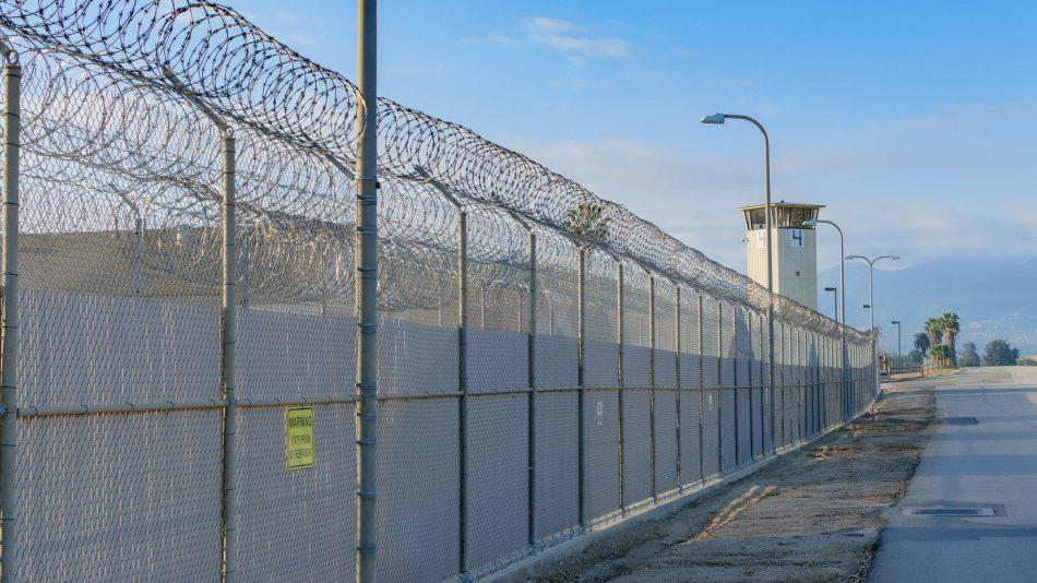 Umfang einer Korrektureinrichtung mit hohem Zaun, der mit Stacheldraht bedeckt ist, und einem Wachturm an der Ecke, um die Einbrucherkennungsfähigkeiten von Senstar zu demonstrieren