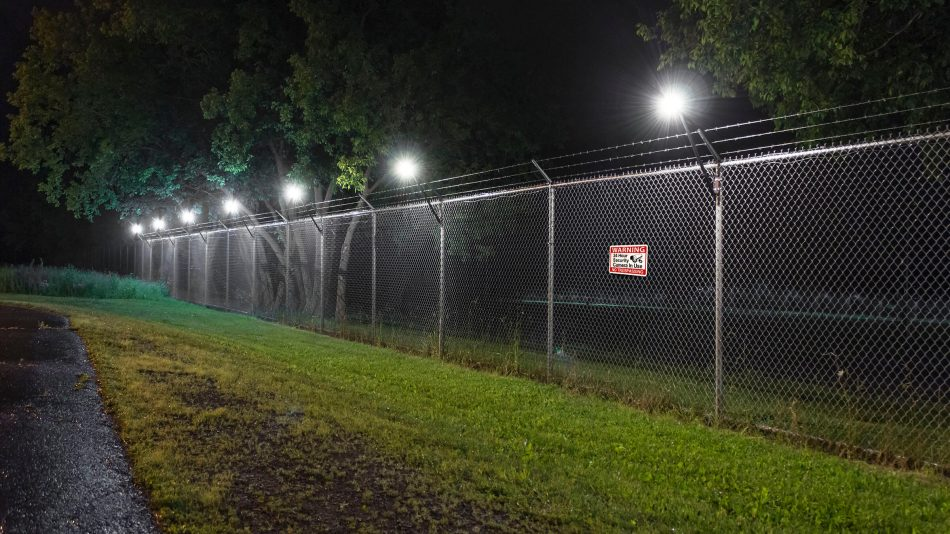 Senstar LM100 hybrid perimeter intrusion detection and intelligent lighting system illuminating a fence line at night