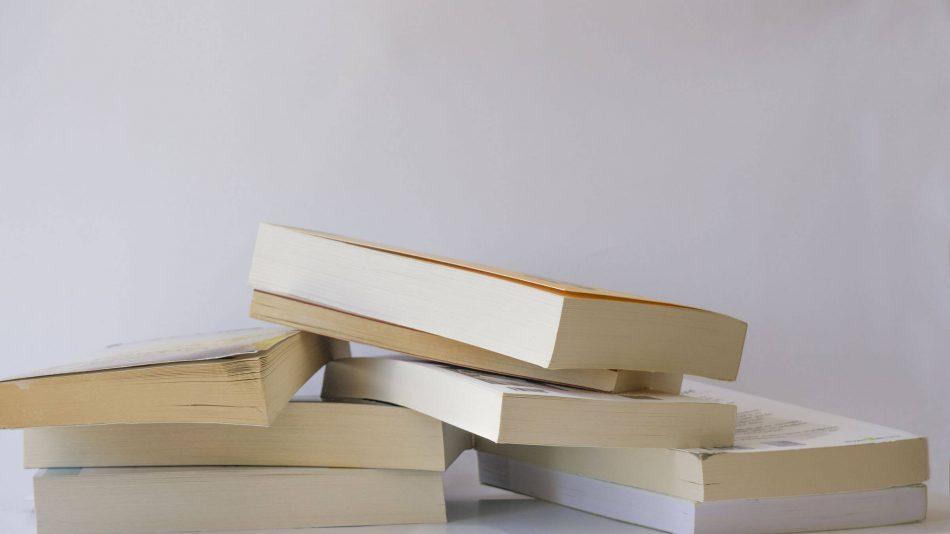 Plusieurs livres éparpillés sur une table pour représenter le savoir dans la base de connaissances de Senstar