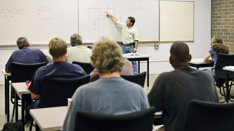 A teacher at a white board with adult students at tables to represent Senstar's technical training courses