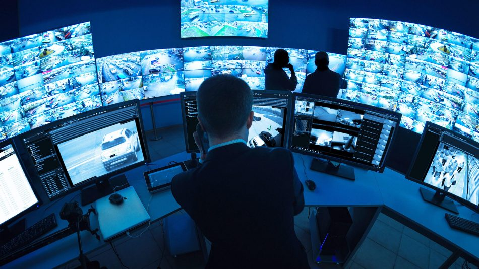 Man in control room with dozens of monitors showing feeds from different cameras, highlighting Senstar Symphony video management capabilities